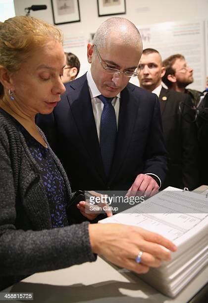 Mikhail Khodorkovsky the former Yukos oil company chairman who was charged with embezzlement and tax evasion looks at a book listing names of victims...