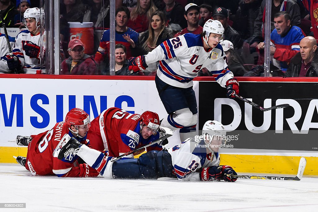 Mikhail Sergachev #26 and teammate Yakov Trenin #25 of Team Russia fall to the ice with Joey Anderson #13 of Team United States while teammate Charlie McAvoy #25 skates by during the 2017 IIHF World Junior Championship semifinal game at the Bell Centre on January 4, 2017 in Montreal, Quebec, Canada. Team United States defeated Team Russia 4-3 in a shootout.