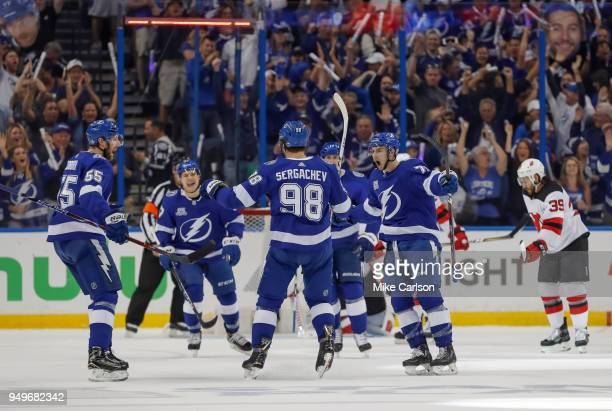 Mikhail Sergachev of the Tampa Bay Lightning is congratulated on his goal by teammates Braydon Coburn and Anthony Cirelli as Brian Gibbons of the New...
