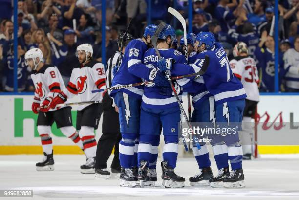 Mikhail Sergachev of the Tampa Bay Lightning is congratulated on his goal by teammates Braydon Coburn and Anthony Cirelli as members of the New...