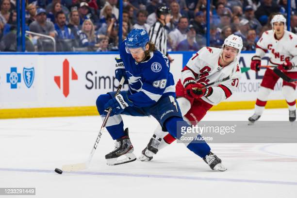 Mikhail Sergachev of the Tampa Bay Lightning skates against Andrei Svechnikov of the Carolina Hurricanes during the second period in Game Four of the...