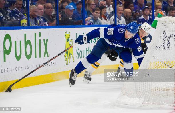 Mikhail Sergachev of the Tampa Bay Lightning skates against Karson Kuhlman of the Boston Bruins during the second period at Amalie Arena on March 25...
