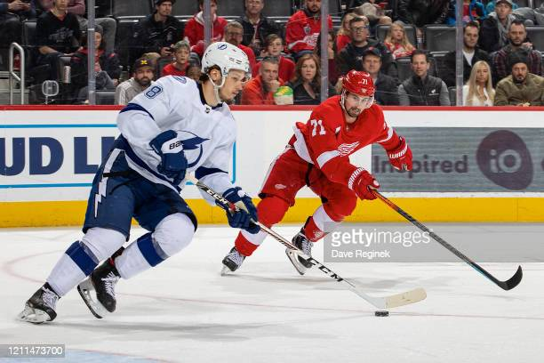 Mikhail Sergachev of the Tampa Bay Lightning skates up ice with the puck next to Dylan Larkin of the Detroit Red Wings during an NHL game at Little...