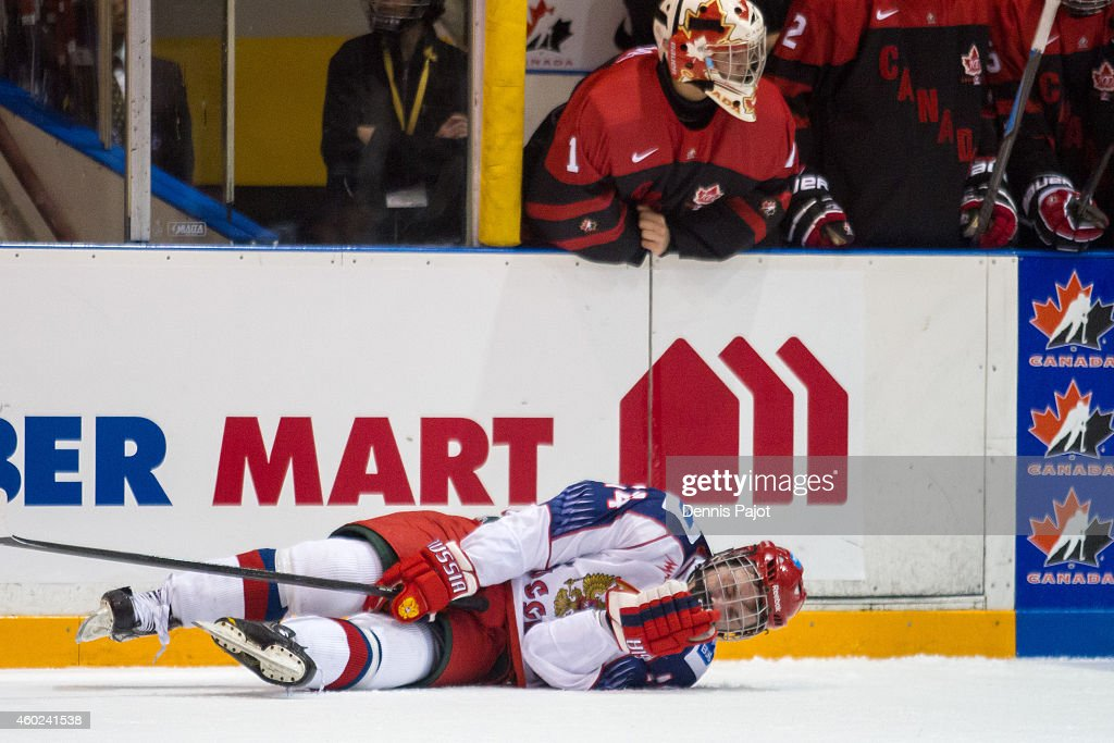 Mikhail Shabanov #14 of Russia is slow to get up after a hit from Nolan Volcan #7 of Canada Black during the World Under-17 Hockey Challenge on November 2, 2014 at the RBC Centre in Sarnia, Ontario.