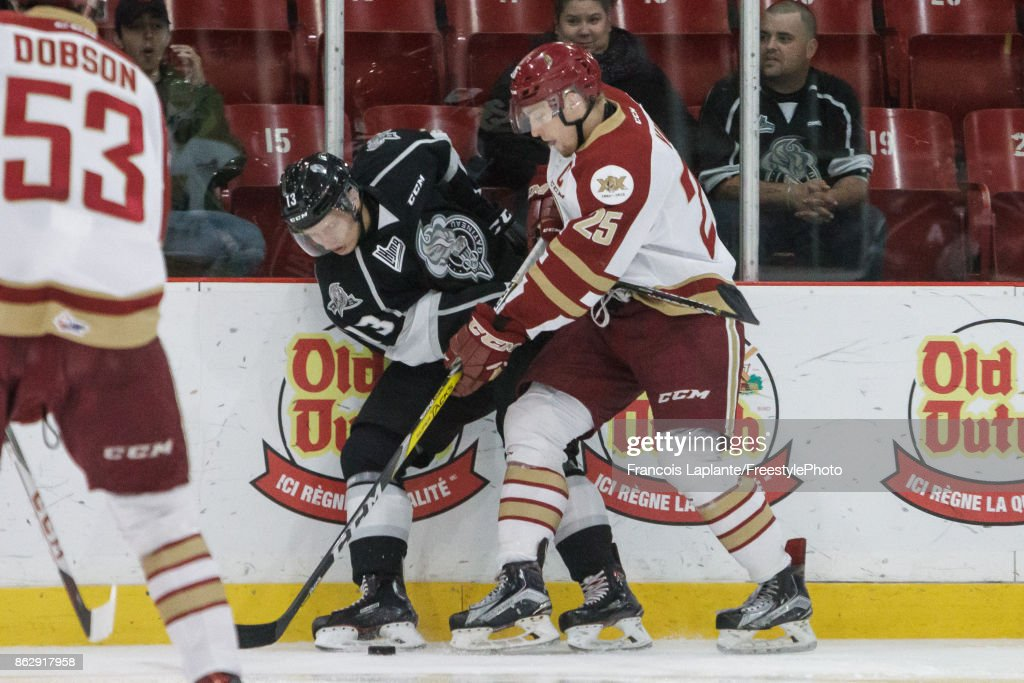Mikhail Shestopalov #13 of the Gatineau Olympiques battles for the puck along the boards against Jeffrey Truchon-Viel #25 of the Acadie-Bathurst Titan on October 18, 2017 at Robert Guertin Arena in Gatineau, Quebec, Canada.