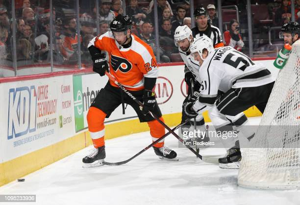 Mikhail Vorobyev of the Philadelphia Flyers battles for the loose puck along the boards with Nate Thompson and Austin Wagner of the Los Angeles Kings...