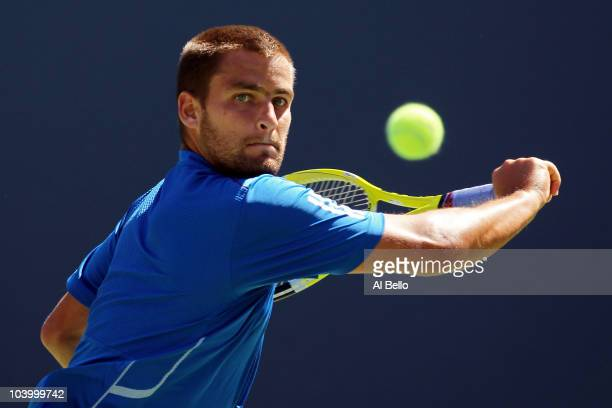 Mikhail Youzhny of Russia returns a shot while playing against Rafael Nadal of Spain during his men's singles semifinal match on day thirteen of the...