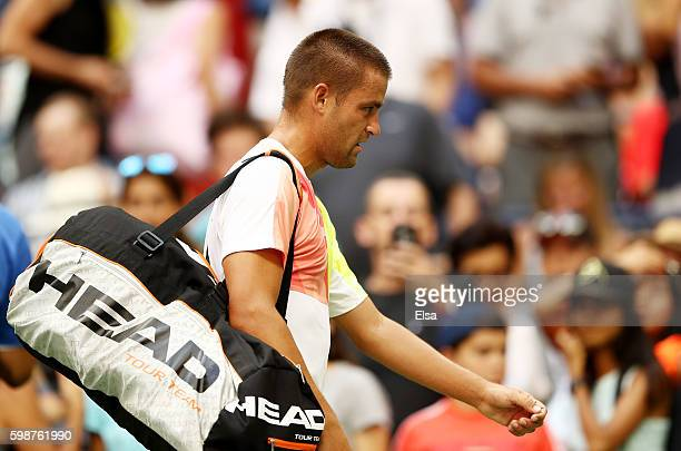 Mikhail Youzhny of Russia walks off the court after retiring to Novak Djokovic of Serbia during his third round Men's Singles match on Day Five of...