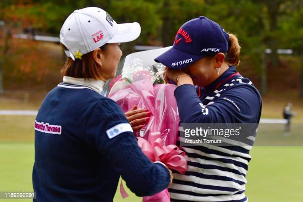 Miki Saiki of Japan shows her emotion as she is presented a flower from Erina Hara after holing out as she had announced not to take the Qualifying...