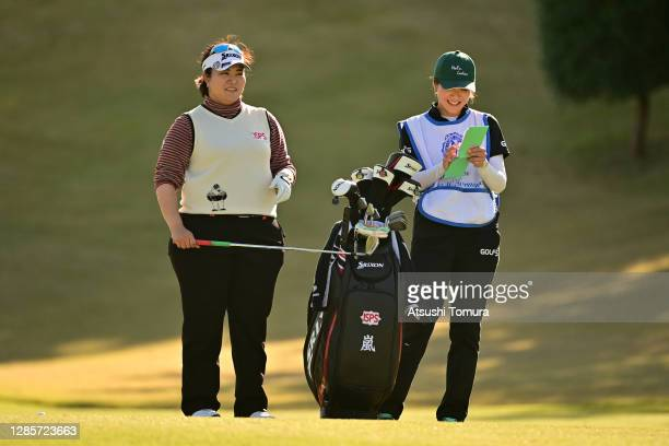 Miki Sakai of Japan talks with her caddie before her third shot on the 15th hole during the final round of the Ito-En Ladies Golf Tournament at the...