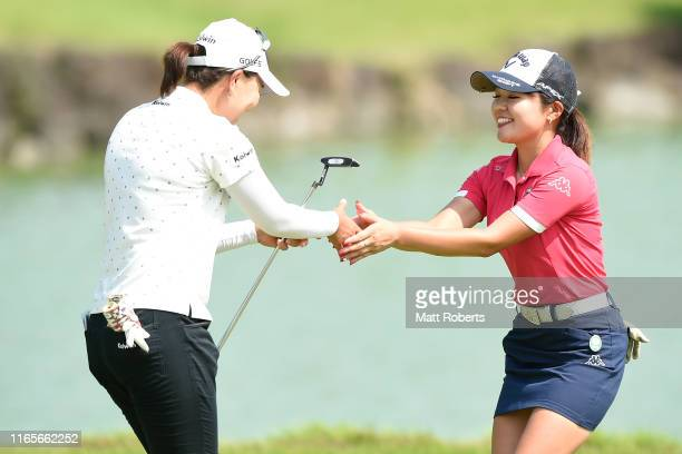 Miki Uehara and Mayu Hirota shake hands after holing out on the 18th green during the final round of the Castol Ladies at Fuji Ichihara Golf Club on...