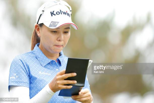 Miki Uehara of Japan checks her yardage book on the 17th hole during the exhibition tournament of the Kanehide Miyarabi Open at Kanehide Kise Country...