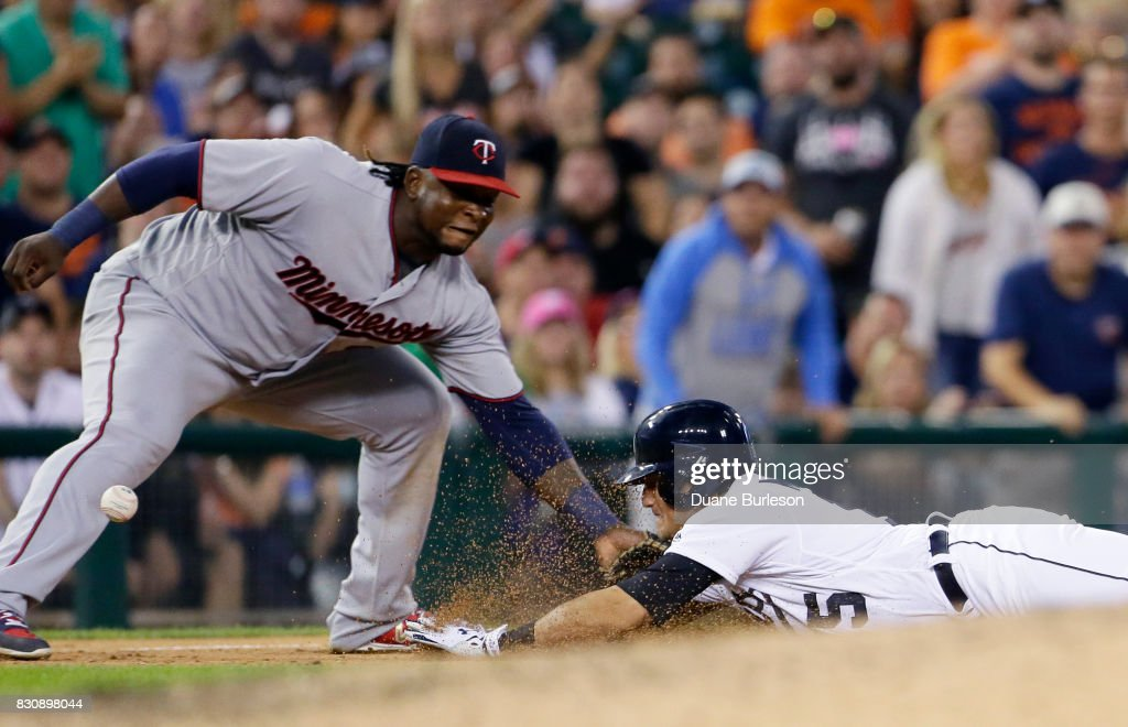 Mikie Mahtook #15 of the Detroit Tigers dives into third base for a triple as third baseman Miguel Sano #22 of the Minnesota Twins can't field the ball that hit Mattoook on the elbow during there seventh inning at Comerica Park on August 12, 2017 in Detroit, Michigan.