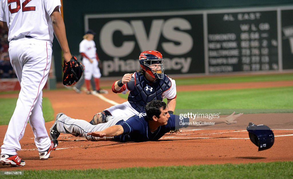 Mikie Mahtook #27 of the Tampa Bay Rays slides into home base safely in the first inning against the Boston Red Sox at Fenway Park on September 21, 2015 in Boston, Massachusetts.