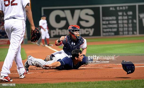 Mikie Mahtook of the Tampa Bay Rays slides into home base safely in the first inning against the Boston Red Sox at Fenway Park on September 21 2015...