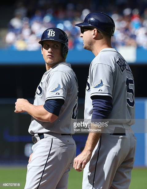 Mikie Mahtook of the Tampa Bay Rays talks to first base coach Rocco Baldelli after drawing a walk in the fifth inning during MLB game action against...