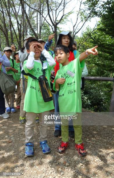 Mikiko Ishihara stands behind her son Shugo at the site of the 1985 Japan Airlines jumbo jet crash in Gunma Prefecture on July 21 2018 Ishihara was a...