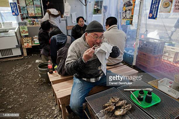 Mikio Junishi eats a charcoal grilled oyster at Ishinomaki City's only oyster restaurant having travelled from from his home in Sendai to support the...