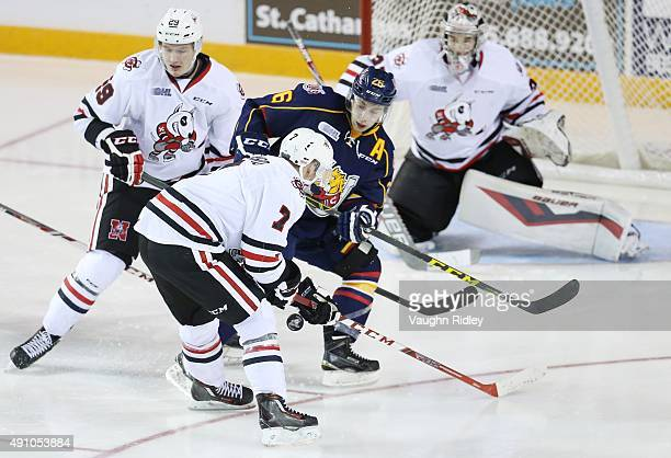 Mikkel Aagaard of the Niagara IceDogs and Andrew Mangiapane of the Barrie Colts battle for the pucks during an OHL game at the Meridian Centre on...