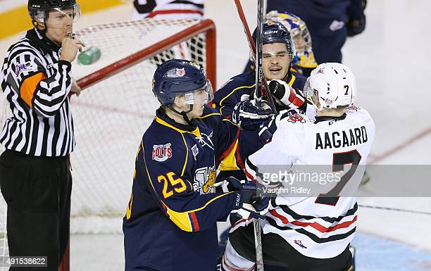 Mikkel Aagaard of the Niagara IceDogs gets into it with Josh Carrick and Julius Nattinen of the Barrie Colts during an OHL game at the Meridian...