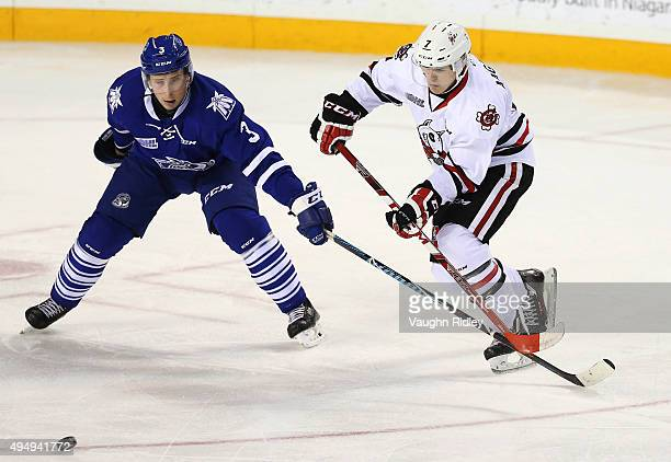 Mikkel Aagaard of the Niagara IceDogs passes the puck as Jared Walsh of the Mississauga Steelheads defends during an OHL game at the Meridian Centre...