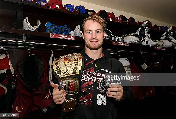 Mikkel Boedker of the Arizona Coyotes holds a game puck from his first career hat trick following a 74 victory against the Edmonton Oilers at Gila...