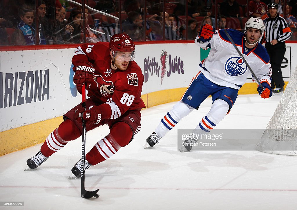 Mikkel Boedker #89 of the Arizona Coyotes skates with the puck ahead of Justin Schultz #19 of the Edmonton Oilers during the NHL game at Gila River Arena on December 16, 2014 in Glendale, Arizona. The Coyotes defeated the Oilers 2-1 in overtime.