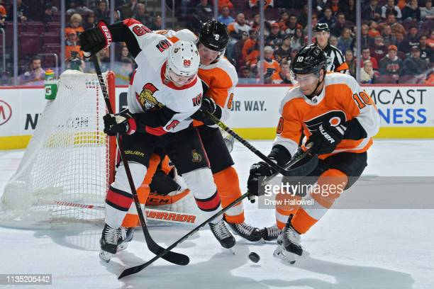 Mikkel Boedker of the Ottawa Senators battles for the puck against Travis Sanheim and Corban Knight of the Philadelphia Flyers in the first period at...