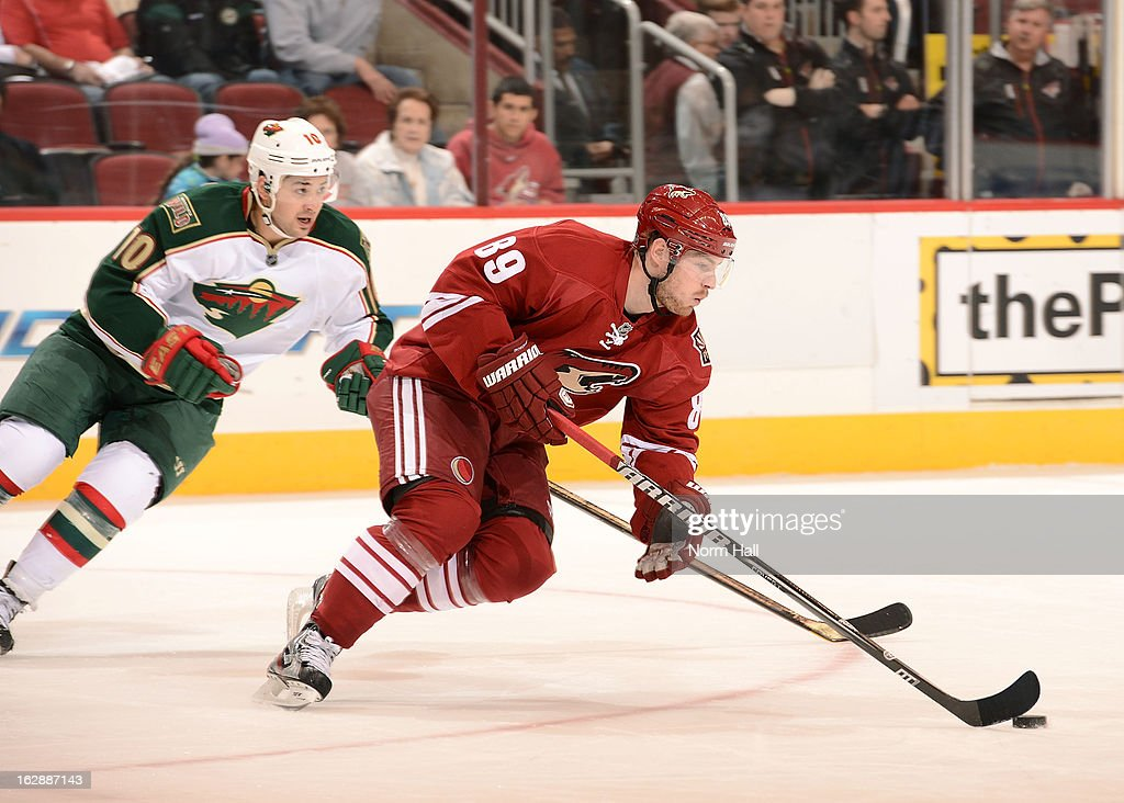 Mikkel Boedker #89 of the Phoenix Coyotes skates the puck up ice past Devin Setoguchi #10 of the Minnesota Wild during the third period at Jobing.com Arena on February 28, 2013 in Glendale, Arizona.