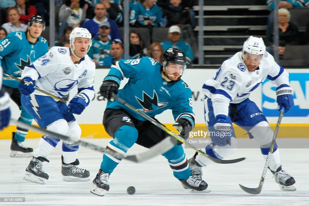 Mikkel Boedker #89 of the San Jose Sharks along with Ryan Callahan #24 and J.T. Brown #23 of the Tampa Bay Lightning chase the puck at SAP Center on November 8, 2017 in San Jose, California.