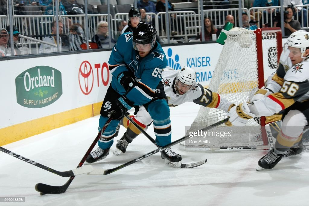 Mikkel Boedker #89 of the San Jose Sharks controls the puck while being defended by Brad Hunt #77 and Erik Haula #56 of the Vegas Golden Knights at SAP Center on February 8, 2018 in San Jose, California.