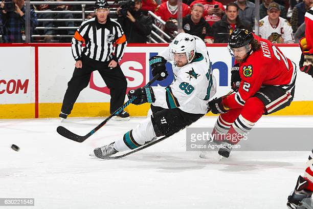 Mikkel Boedker of the San Jose Sharks hits the puck ahead of Duncan Keith of the Chicago Blackhawks in the third period at the United Center on...