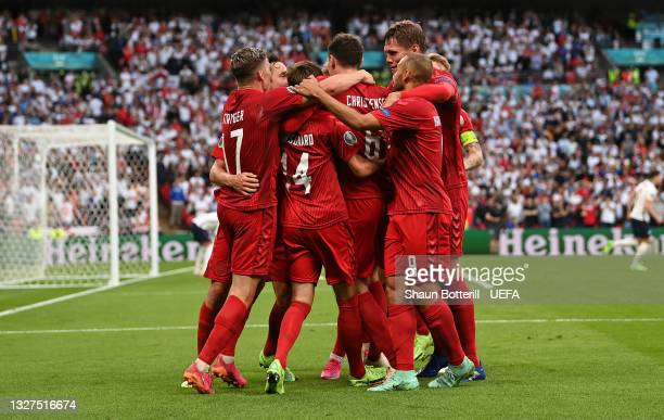 Mikkel Damsgaard of Denmark celebrates with teammates after scoring their team's first goal during the UEFA Euro 2020 Championship Semi-final match...