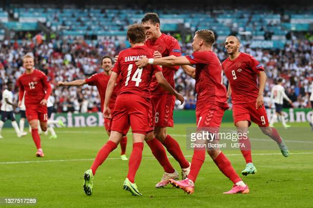Mikkel Damsgaard of Denmark celebrates with teammates Andreas Christensen and Jens Stryger Larsen after scoring their team's first goal during the...