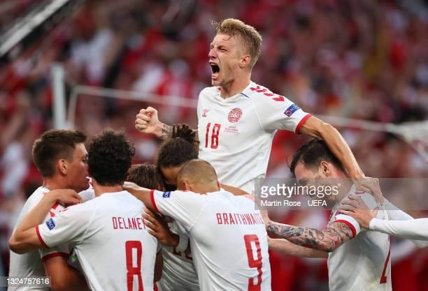 Mikkel Damsgaard of Denmark celebrates with teammates Daniel Wass, Martin Braithwaite, Joakim Maehle and Thomas Delaney after scoring their side's...