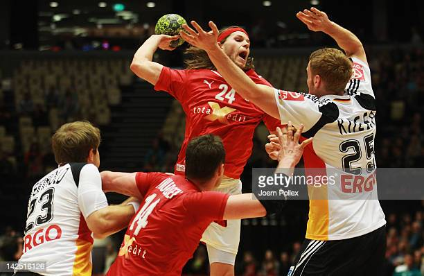 Mikkel Hansen of Denmark is challenged by Stefan Kneer of Germany during the Handball international friendly match between Denmark and Germany at...