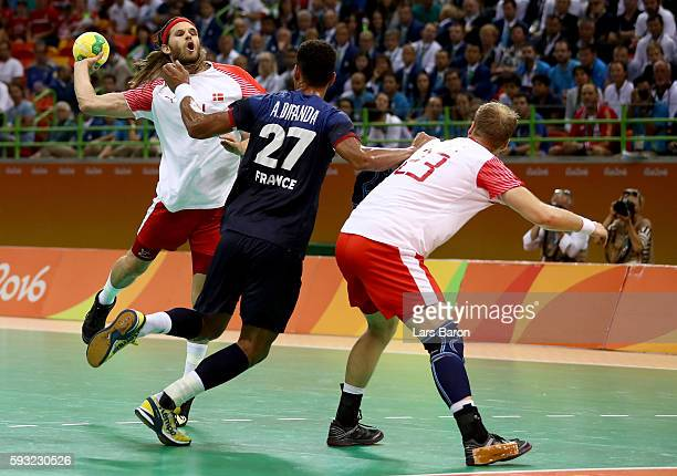 Mikkel Hansen of Denmark jumps to shoot against Adrien Dipanda of France during the first half in the Men's Gold Medal Match between Denmark and...