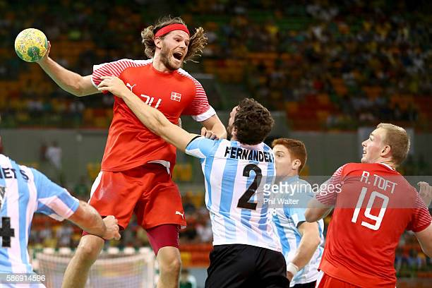 Mikkel Hansen of Denmark shoots at goal past Federico Fernandez of Argentina during the Mens Preliminary Group A match between Denmark and Argentina...