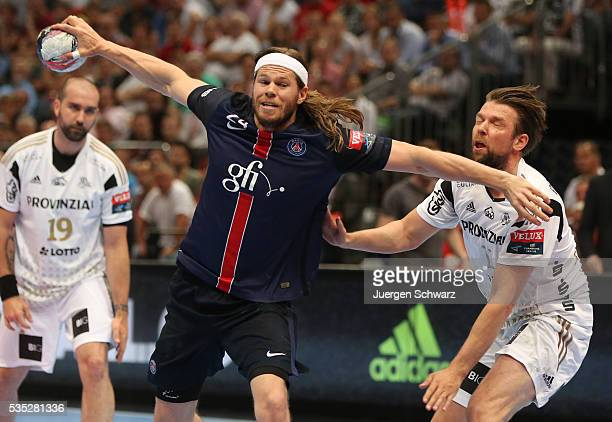 Mikkel Hansen of Paris throws the ball beside Christian Sprenger of Kiel during the third place playoff at the EHF Final4 between Paris StGermain and...