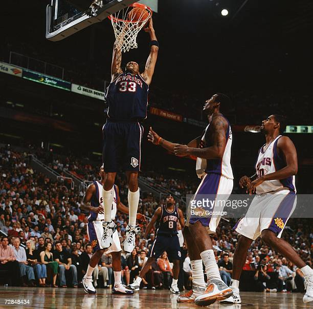 Mikki Moore of the New Jersey Nets takes the ball to the basket against Amare Stoudemire and of the Phoenix Suns during a game at US Airways Center...
