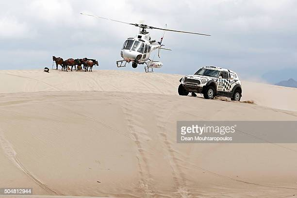 Mikko Hirvonen of Finland and Michel Perin of France in the MINI ALL4 RACING for AXION XRAID TEAM are followed by the TV helicopter as they pass a...