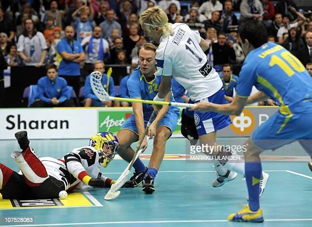 Mikko Kohonen of team Finland tries to score pass Sweden's goalie Patrik Jansson and defenders Rasmus Sundstedt and Mathias Larsson during the World...