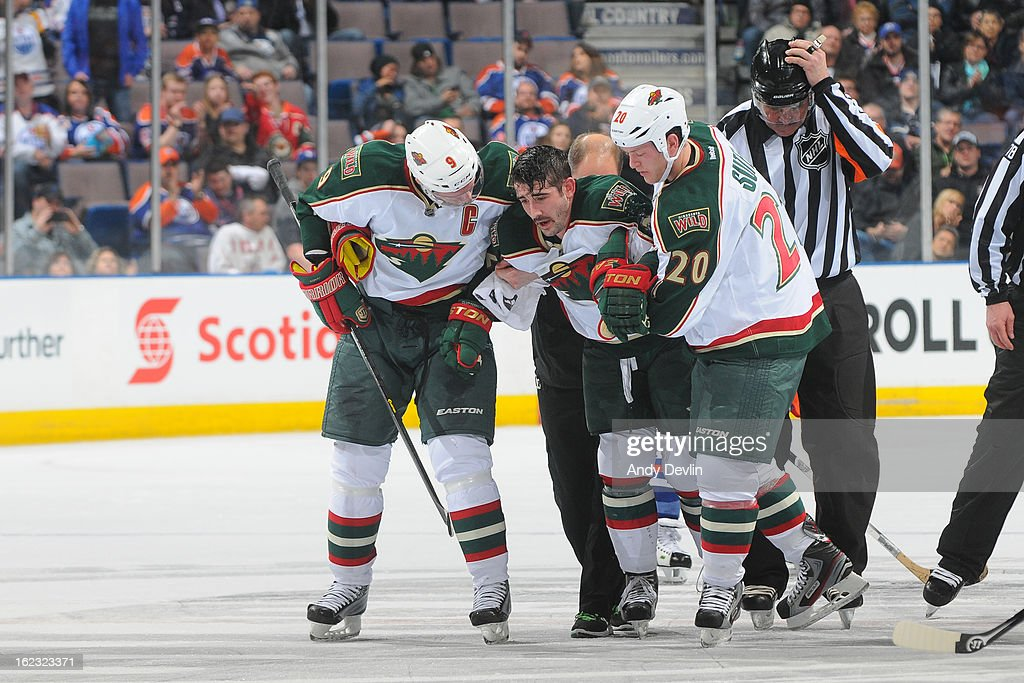Mikko Koivu #9 and Ryan Suter #20 of the Minnesota Wild help team mate Cal Clutterbuck #22 off the ice after sustaining an injury late in the game against the Edmonton Oilers on February 21, 2013 at Rexall Place in Edmonton, Alberta, Canada.