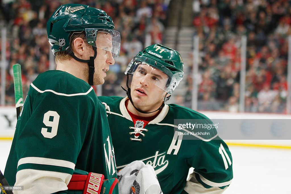 Mikko Koivu #9 and Zach Parise #11 of the Minnesota Wild talk during a break in the game against the Detroit Red Wings on February 17, 2013 at the Xcel Energy Center in Saint Paul, Minnesota.