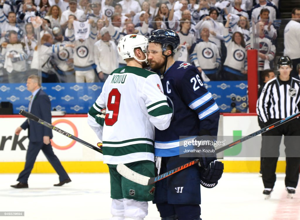 Mikko Koivu #9 of the Minnesota Wild and Blake Wheeler #26 of the Winnipeg Jets share an embrace in the handshake line following a 5-0 Jets victory in Game Five of the Western Conference First Round during the 2018 NHL Stanley Cup Playoffs at the Bell MTS Place on April 20, 2018 in Winnipeg, Manitoba, Canada. The Jets win the series 4-1.