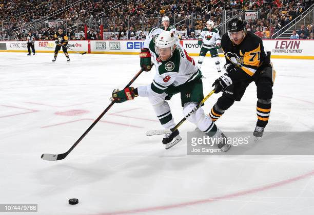 Mikko Koivu of the Minnesota Wild and Evgeni Malkin of the Pittsburgh Penguins battle for the loose puck at PPG Paints Arena on December 20 2018 in...