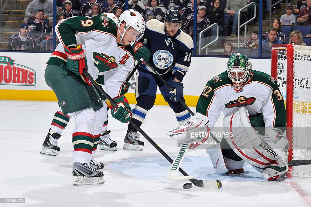 Mikko Koivu #9 of the Minnesota Wild attempts to clear the puck against the Columbus Blue Jackets during the first period on April 7, 2013 at Nationwide Arena in Columbus, Ohio.
