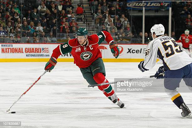 Mikko Koivu of the Minnesota Wild attempts to make a move around defense Shane O'Brien of the Nashville Predators during the game at Xcel Energy...