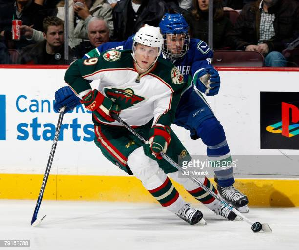 Mikko Koivu of the Minnesota Wild carries the puck as Taylor Pyatt of the Vancouver Canucks skates after him during their game at General Motors...