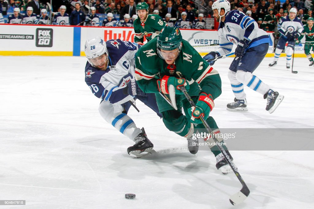 Mikko Koivu #9 of the Minnesota Wild skates with the puck while Blake Wheeler #26 of the Winnipeg Jets defends during the game at the Xcel Energy Center on January 13, 2018 in St. Paul, Minnesota.